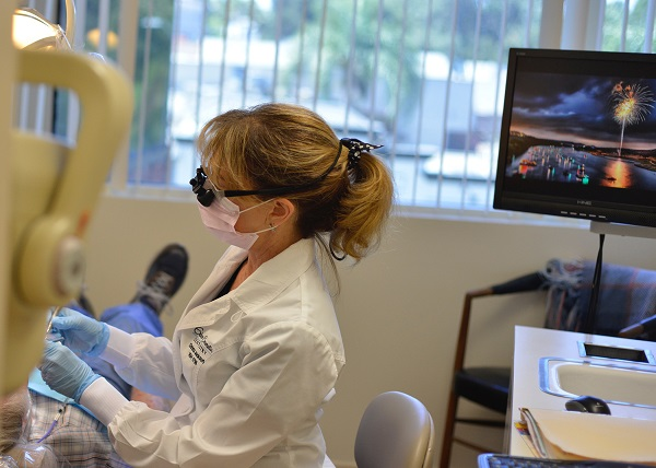 Encino dentist, Roberta Cerveny providing a cleaning and exam to a patient at Encino Cosmetic Dentistry.